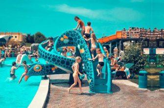 Вокруг бассейнов, детских горок стоят многочисленные лежаки
